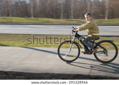 Boy ten years of age on the bike in spring looks to the camera and rides - stock photo