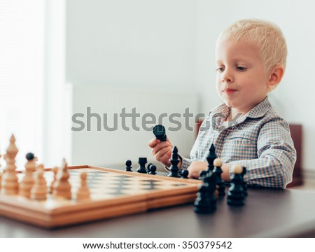Boy thinking about how to play the next move in chess - stock photo