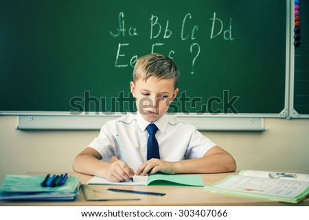 Boy thinking and sits at a desk at school with glasses and writes in a notebook. Against the background of the school board english alphabet. Schoolboy dressed in a school uniform. - stock photo