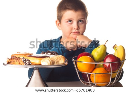 boy thinking over a healthy snack or a dessert - stock photo