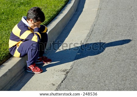Boy thinking sitting on the curve. - stock photo
