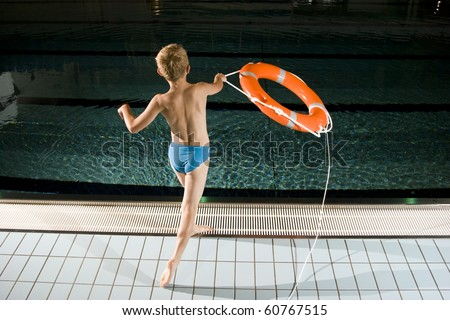 Boy throwing lifebuoy on swimming pool - stock photo