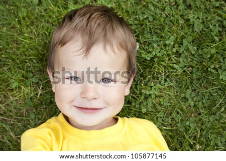 boy toddler is relaxing in the grass during summer days