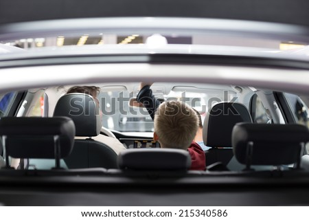 Boy touching the overhead panel of new modern car - stock photo