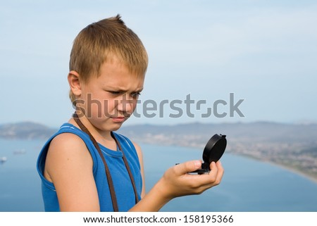 Boy tourist looking at the compass being on top of the mountain. - stock photo