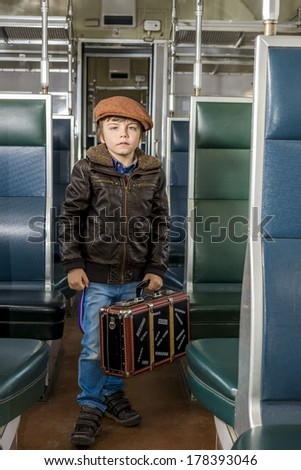 boy traveling in a train with his suitcase - stock photo