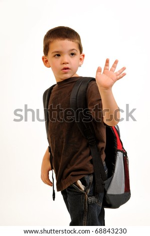 Boy, turning back and waving goodbye heading off to school. - stock photo