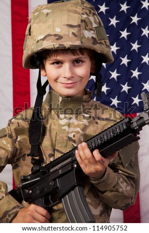 Boy USA soldier in front of American flag with rifle. Young boy dressed like a soldier