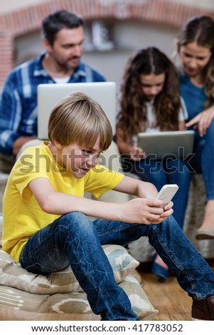 Boy using a mobile phone while family sitting on a sofa in background - stock photo