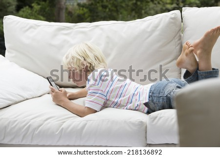 Boy using digital tablet on outdoor sofa - stock photo