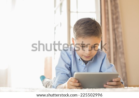 Boy using digital tablet while lying on floor at home - stock photo