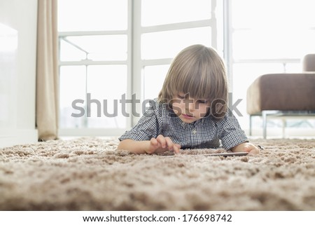 Boy using digital tablet while lying on rug in living room - stock photo