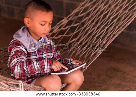 Boy using digital tablet while sitting on crib at home - stock photo