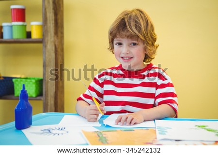 Boy using scissors to cut paper at the desk