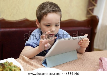 Boy using tablet PC in a cafe