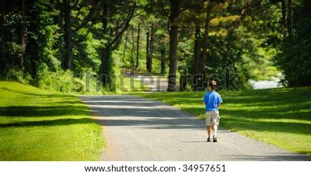 Boy walking at the park - stock photo