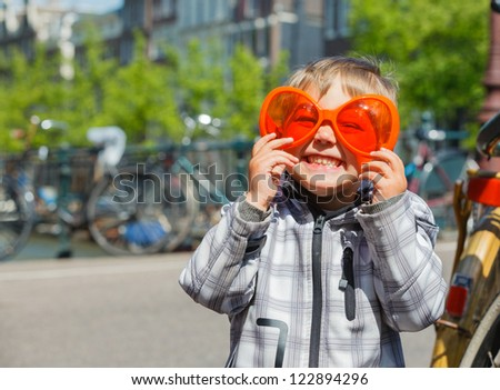 Boy walking in orange glasses for Dutch Queensday on the Amsterdam street - stock photo