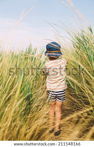 boy walking through grass following the path - stock photo