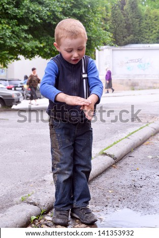 boy washes his hands dirty in a puddle - stock photo