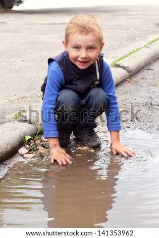 boy washes his hands dirty in a puddle