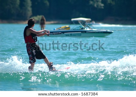 Boy watching a girl while water skiing - stock photo