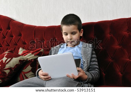 Boy watching portable DVD player in a cafe. - stock photo