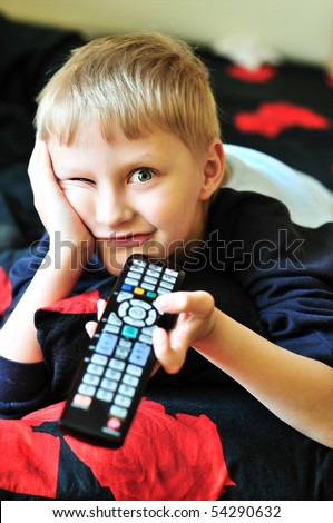 boy watching tv, laying in bad and making face - stock photo