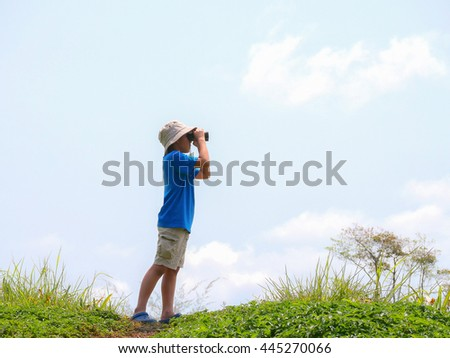 Boy wearing a hat standing on a grassy knoll sunny. Use binoculars to explore the world