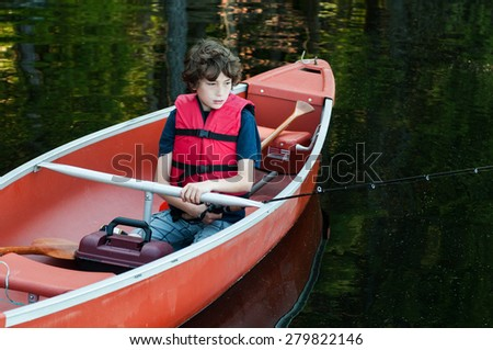 boy wearing a life jacket fishing in a canoe - stock photo
