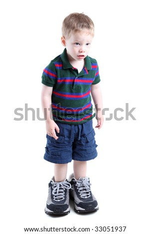 Boy wearing big sneakers isolated on white