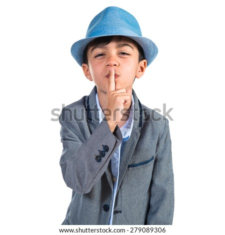 Boy wearing blue hat making silence gesture  - stock photo