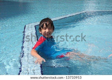 Boy wearing blue & red swim suit at the pool - stock photo