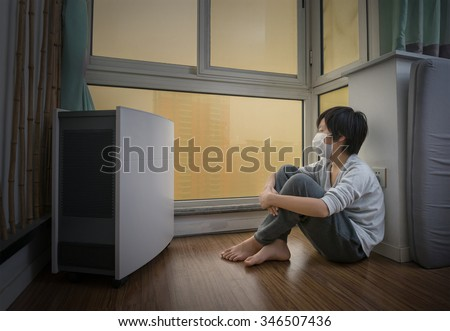 Boy wearing mouth mask at home near air purifier on an extremely polluted day - stock photo