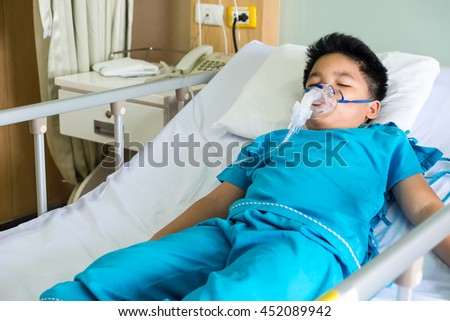 Boy wearing oxygen mask in hospital ward, sleep on bed. Selective focus.