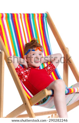 Boy wearing swimming goggles sitting on beach chair. Isolated On White Background. - stock photo