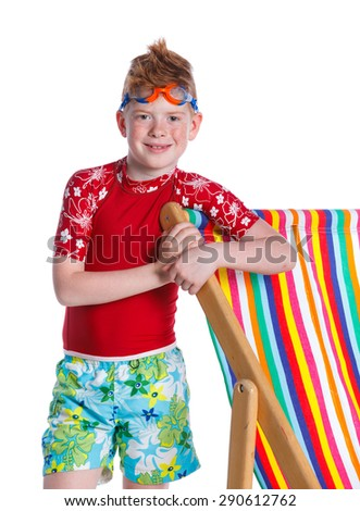 Boy wearing swimming goggles standing near beach chair. Isolated On White Background. - stock photo