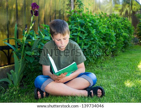 boy with a book on the grass on a sunny day - stock photo