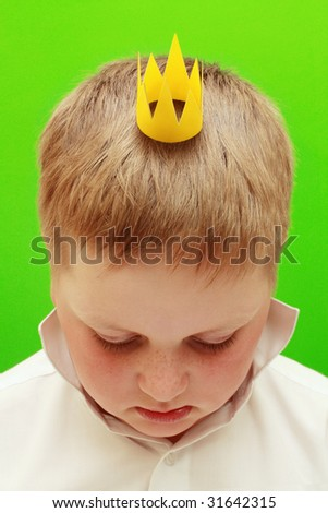 Boy with a crown on a green background - stock photo