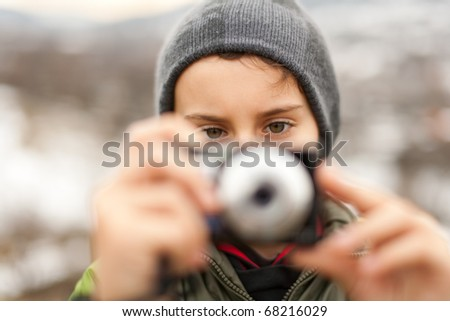 Boy with a digital camera taking pictures outdoor - stock photo