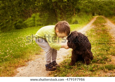 boy with a dog walking in the park. Child playing with the dog