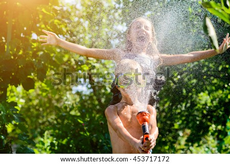Boy With A Girl Playing In The Hot Summer, Spraying Each Other With Water  From
