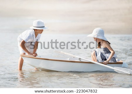 Boy with a girl riding on a boat on the lake in summer sunny day - stock photo