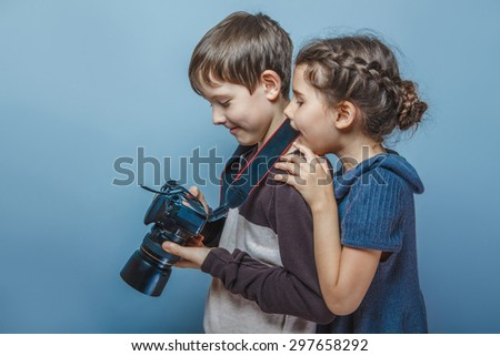 Boy with a girl watching pictures on the  camera  on a gray  background - stock photo