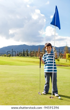 Boy with a golf flag in the hole at the course - stock photo