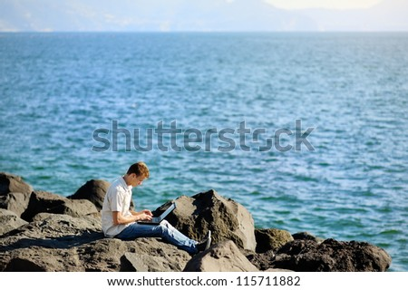 boy with a laptop sitting on a rock by the sea