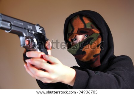 Boy with a mask suggesting a young criminal (delinquent) or a terrorist - stock photo