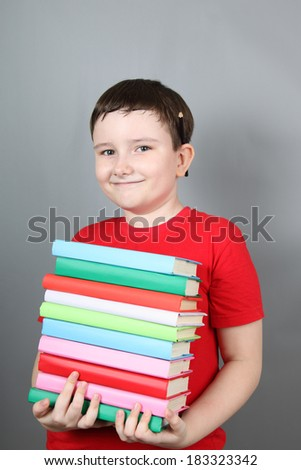 Boy with a pile of books on a gray background. - stock photo