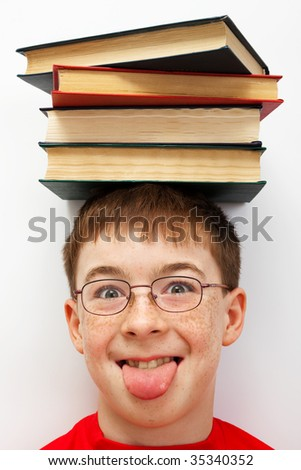 boy with a pile of books on her head - stock photo
