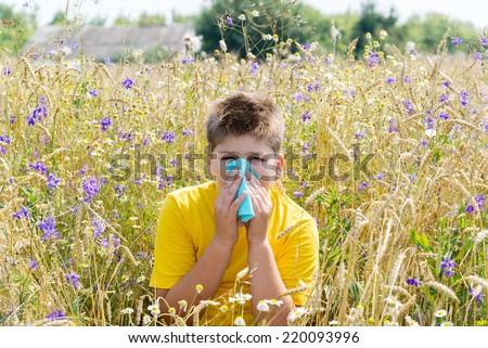 Boy with allergic rhinitis in the meadow - stock photo