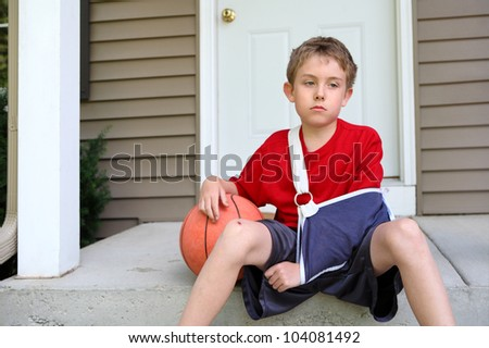 Boy with arm in a sling sitting with a basketball - stock photo